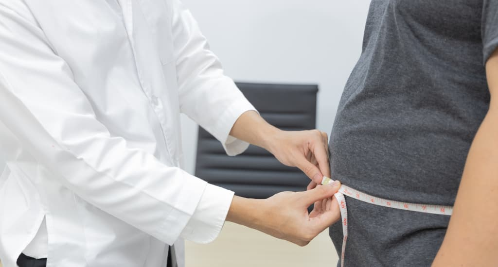Doctor measuring the waist of a patient